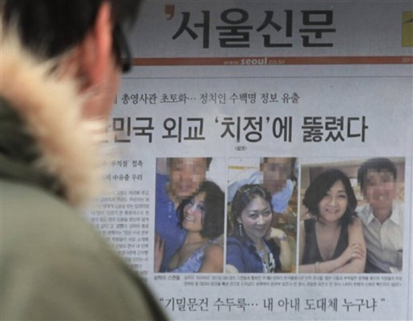 """A South Korean man reads a newspaper with photos showing a Chinese woman Deng Xinming poses with South Korean diplomats, on the street in Seoul, South Korea, Wednesday, March 9, 2011. South Korea's Foreign Minister Kim Sung-hwan has offered a public apology over an alleged sex scandal involving several diplomats and a Chinese mistress. The headline says, """"'Crime of passion' penetrated South Korean diplomacy."""" (AP Photo/Ahn Young-joon)"""