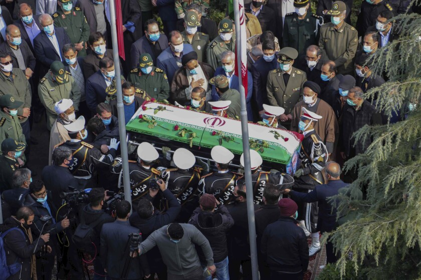 "In this photo released by the official website of the Iranian Defense Ministry, military personnel carry the flag draped coffin of Mohsen Fakhrizadeh, a scientist who was killed on Friday, in a funeral ceremony in Tehran, Iran, Monday, Nov. 30, 2020. Iran held the funeral service for Fakhrizadeh, who founded its military nuclear program two decades ago, with the Islamic Republic's defense minister vowing to continue the man's work ""with more speed and more power."" (Iranian Defense Ministry via AP)"