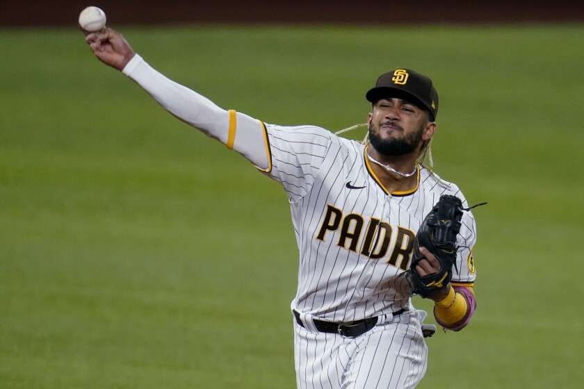 San Diego Padres' Fernando Tatis Jr. fields a ground out by Los Angeles Dodgers' Mookie Betts during the first inning in Game 3 of a baseball National League Division Series Thursday, Oct. 8, 2020, in Arlington, Texas. (AP Photo/Sue Ogrocki)