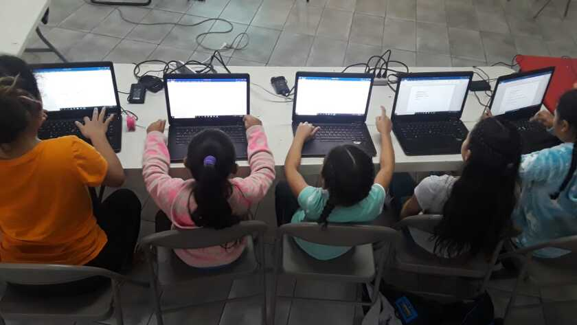 Girl at Tijuana migrant shelter Espacio Migrante learn basic computer skills through a program made in partnership with Create Purpose and UC San Diego.