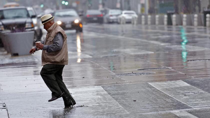 Un hombre brinca entre los charcos de la lluvia en la calle Broadway en el centro de Los Angeles.