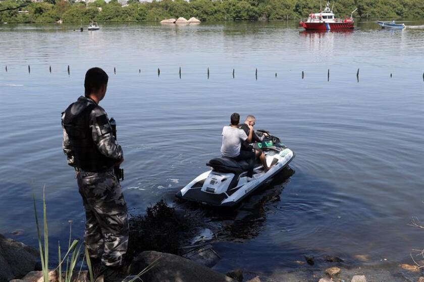 Police officers search for the victims of a helicopter that fell in the bay of Guanabara in Rio de Janeiro, Brazil. EPA- EFE/ Antonio Lacerda