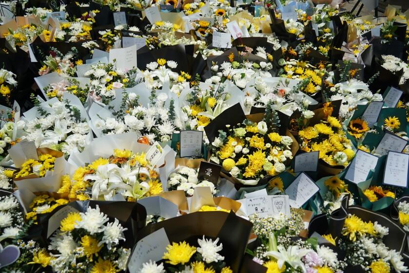 En esta imagen del 27 de julio de 2021, ramos de flores a la entrada de una estación de metro en Zhengzhou, en la provincia china de Henan, donde murieron varias personas cuando unas lluvias históricas inundaron la zona. (AP Foto/Dake Kang, Archivo)