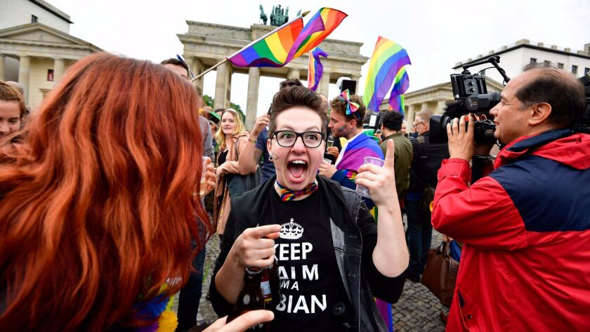 People celebrate at a rally in front of the Brandenburg Gate in Berlin.