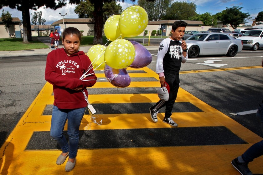 Leslie Corrales, 10, left, and her cousin bring balloons to a makeshift memorial where three 13-year-old girls, two of whom were twins, were killed by a hit-and-run driver Friday evening while they were trick-or-treating in Santa Ana.