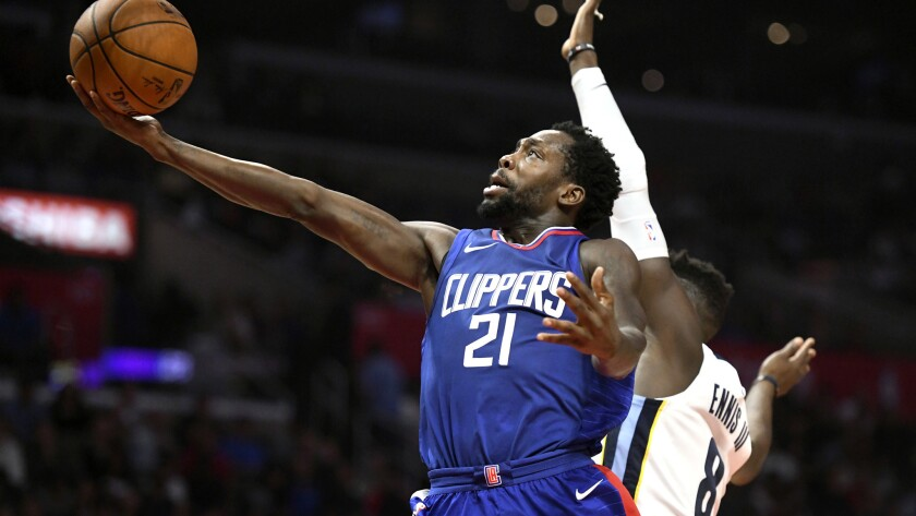 Clippers guard Patrick Beverley attempts a layup against Grizzlies forward James Ennis III during a game Nov. 4.