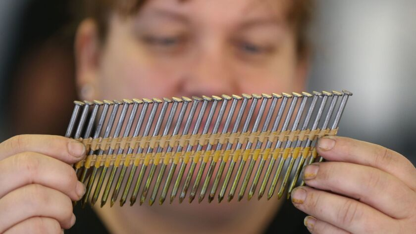 A worker at Mid Continent Nail Corp. looks at a set of nails at the company' production factory in Missouri.