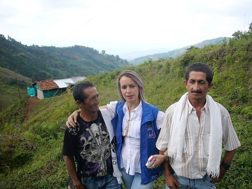 Juan Manuel Ospina, left, formerly with the Revolutionary Armed Forces of Colombia, got help from Liliana Gallego, center, in joining a farming program to help reintegrate into society. At right is Ospina's brother Wilson, himself a former paramilitary fighter.