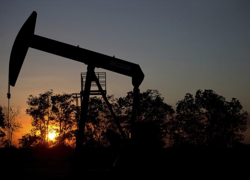The sun sets behind an oil well in a field near El Tigre, Venezuela, in 2015.