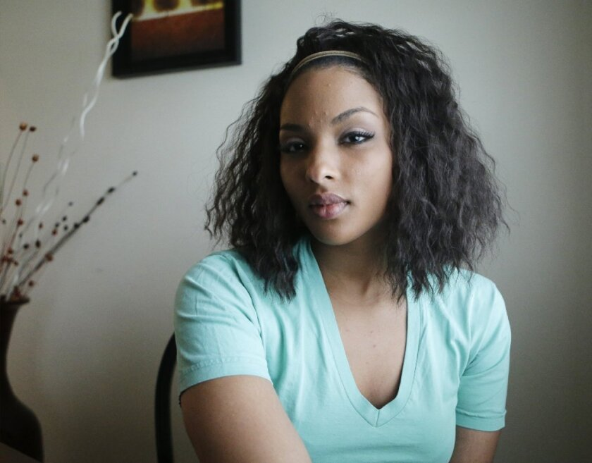 Sakeena Majeed sits in the living room of her mother's home in Cleveland Friday, Dec. 19, 2014. The 24-year-old Muslim woman has filed a federal lawsuit against Cuyahoga County, alleging she was forced to attend Christian church services during a 60-day jail stint on an assault charge.