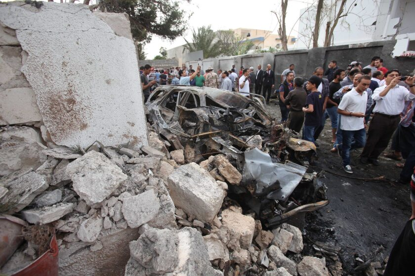 Libyan security forces gather outside the French Embassy in Tripoli following a car bomb blast.