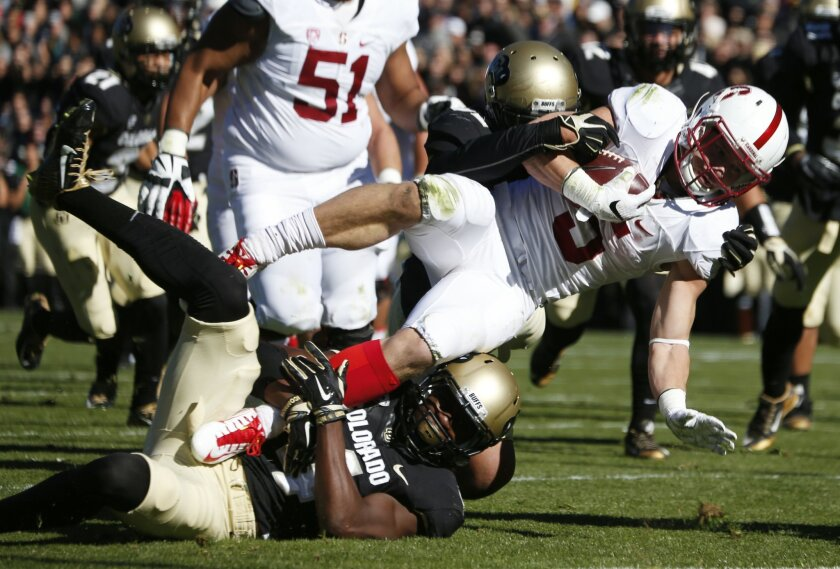 Stanford running back Christian McCaffrey, top, is stopped short of the goal line by Colorado defensive back Chidobe Awuzie, bottom, as linebacker Kenneth Olugbode comes in from behind in the first half of an NCAA football game Saturday, Nov. 7, 2015, in Boulder, Colo. (AP Photo/David Zalubowski)