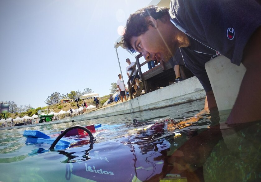"""Felipe Jared Guerrero Moreno, a member of the Mechatronics Club at San Diego State University, prepares to release """"Defiance,"""" the group's autonomous underwater Vehicle, during the 18th annual International RoboSub Competition at SPAWAR facility in Point Loma."""