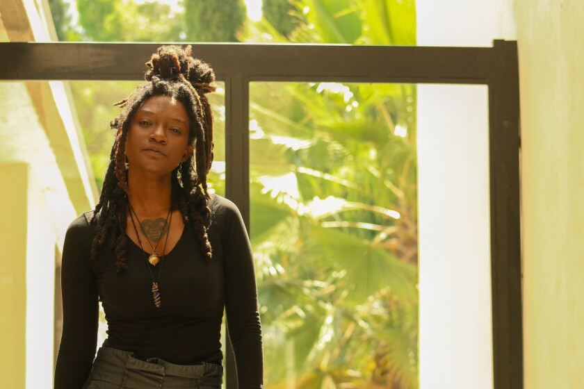 Ebonay Lee, looking at the camera with chin slightly raised, standing in front of a window showing a view of palm leaves