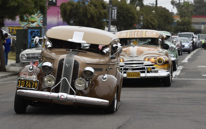 Lowriders cruise down Logan Ave during the La Vuelta Car Cruise event