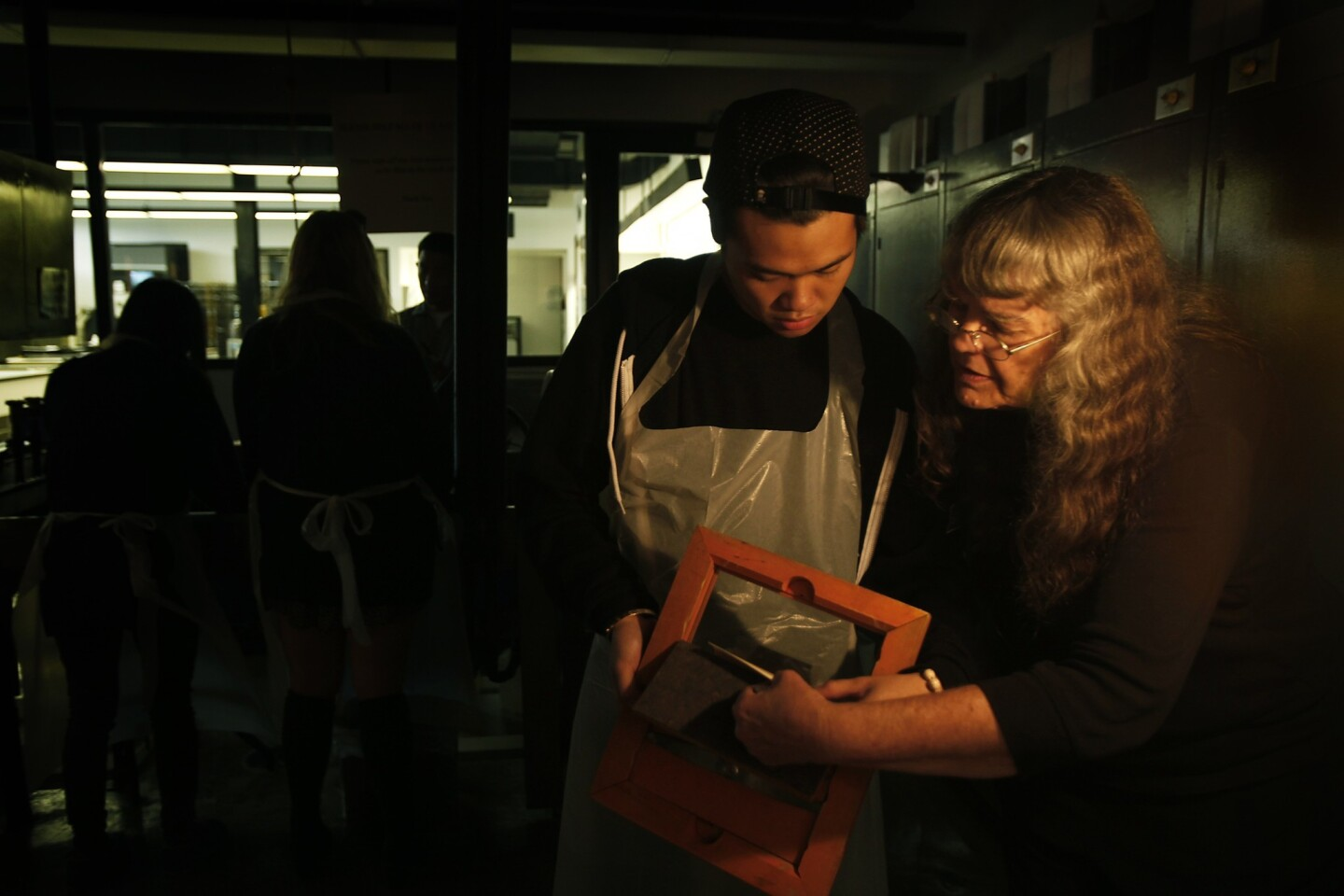 Julian Latif, 22, listens to Norma Smith as she explains platinum printing at the Art Center College of Design in Pasadena.