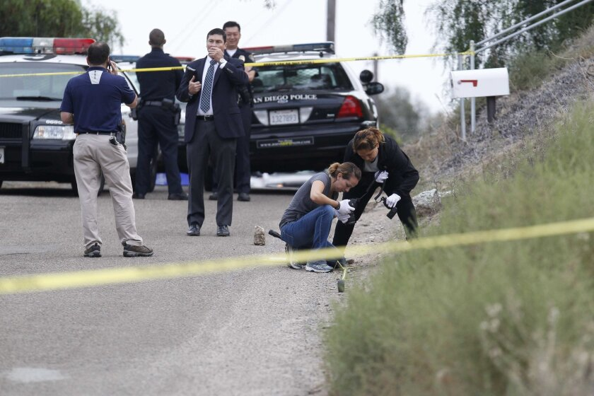 San Diego Police homicide investigators at the site of a slaying in Encanto in September. A man who had been stabbed died as officers and paramedics tried to save him.