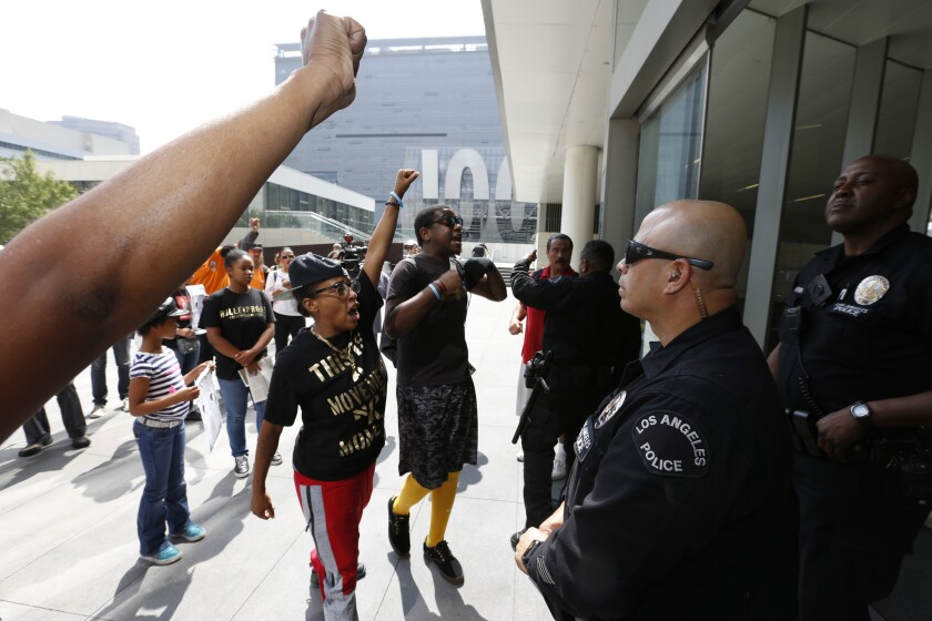 Protesters shout their message in the face of an LAPD officers after disrupting the Los Angeles Police Commission meeting on the one-year anniversary of Ezell Ford's death. Ford was a 25-year-old mentally ill black man who was shot dead by LAPD officers in August 2014.