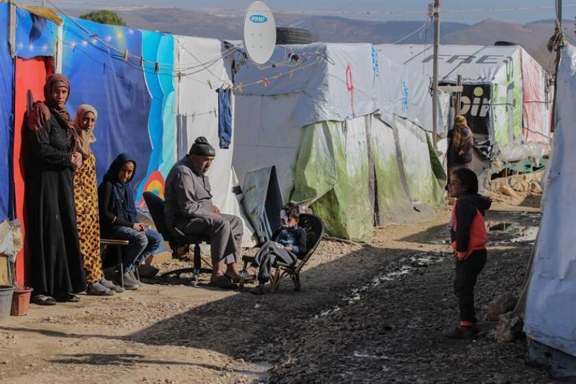 Vista este miércoles de familias de refugiados sirios sentadas al sol frente a sus tiendas de campaña. EFE/Archivo