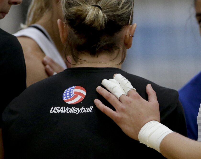 In this Tuesday, May 24, 2016, photo, Kayla Banwarth gets a pat of the back during U.S. women's national volleyball team practice in Anaheim, Calif. When the U.S. women's volleyball team got together months ago, the coaches embarked on a risky experiment: Evaluate your teammates. It paid off in a s