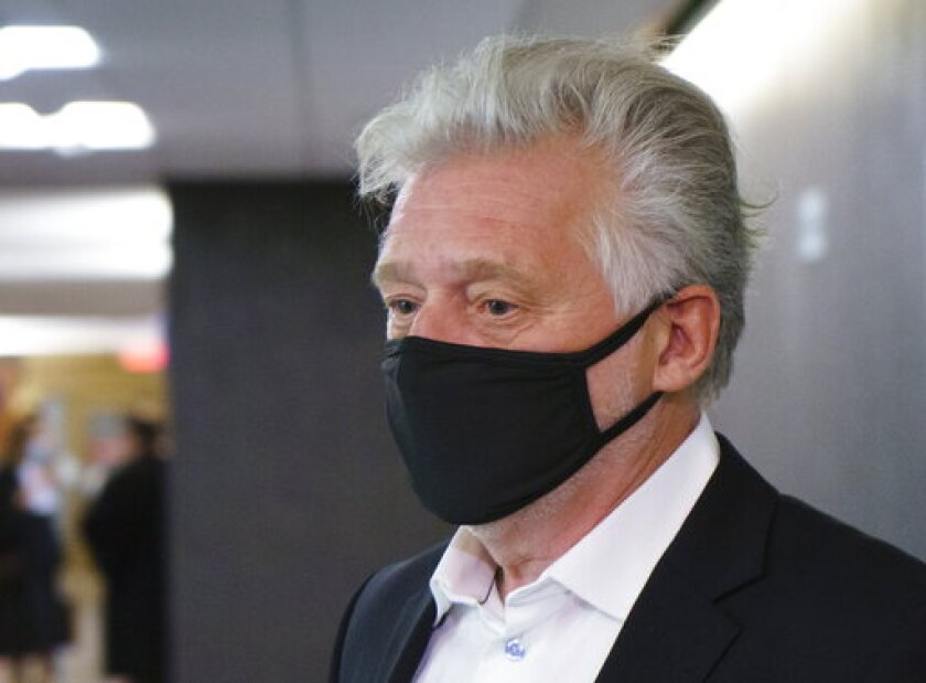 Just for Laughs founder Gilbert Rozon walks the hall of the courthouse as he arrives for the beginning of his sexual assault trial in Montreal on Tuesday, Oct. 13, 2020. (Paul Chiasson/The Canadian Press via AP)