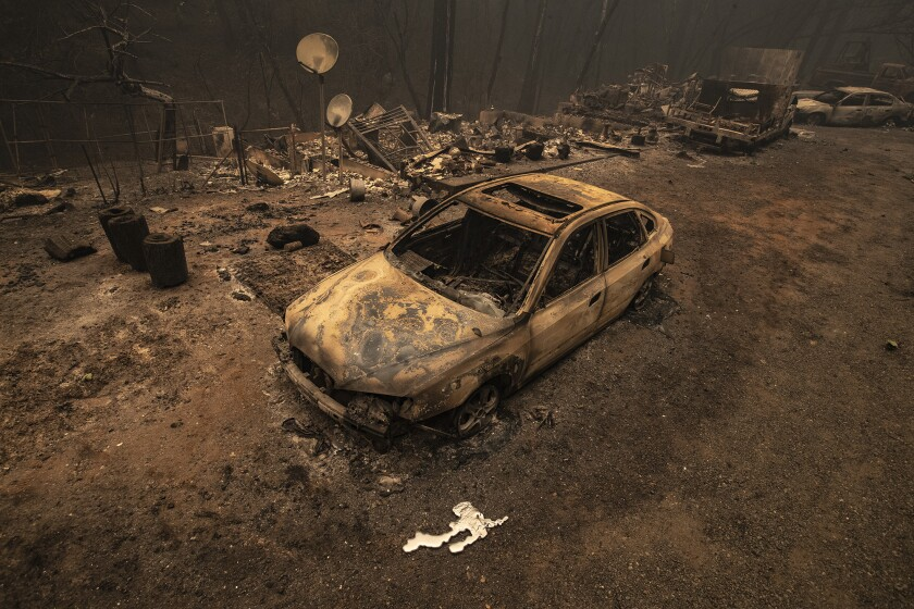 A scorched car sits in front of the remnants of a burned home