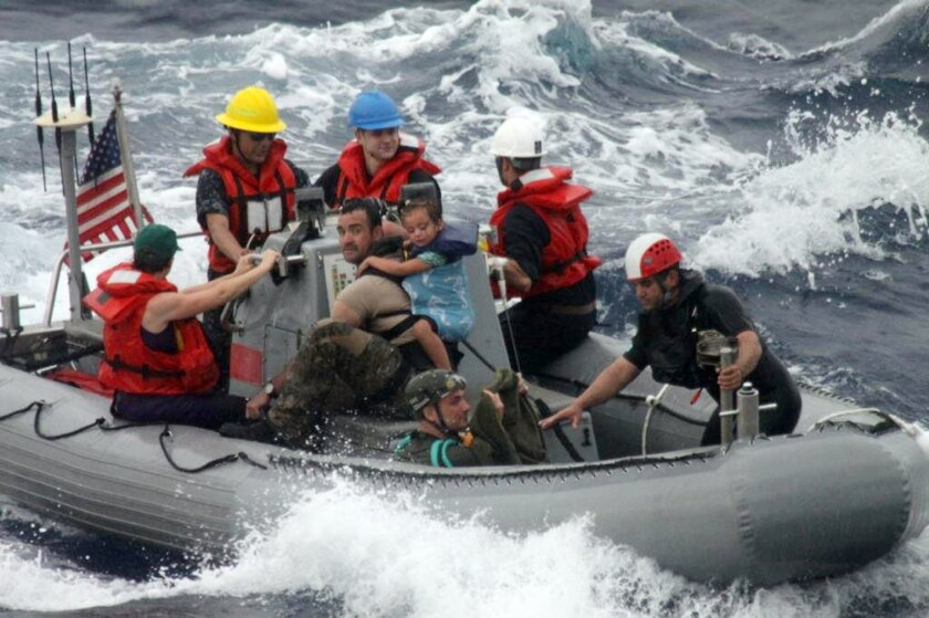 In this photo provided by the U.S. Coast Guard, sailors from Oliver Hazard Perry-class frigate USS Vandegrift (FFG 49) assist in the rescue of a family with a sick infant via the ship's small boat as part of a joint U.S. Navy, Coast Guard and California Air National Guard rescue effort, Sunday, Apr