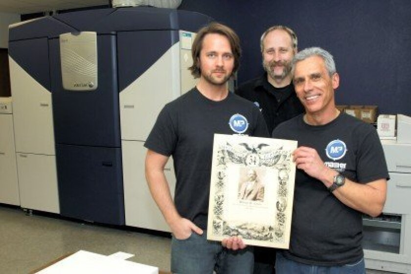 Master Print Communications staff members Zeb Ekeroth, Joshua Miskovsky and Michael Bocskovits with the limited edition graphic honoring William H. Carney. Photo/Jon Clark