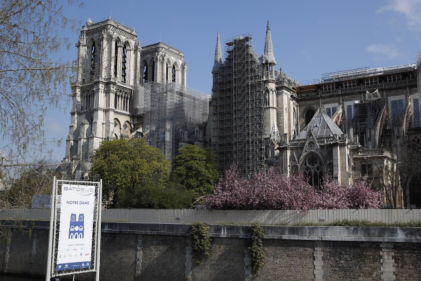 FILE - In this file photo dated Thursday, April 15, 2021, Notre Dame cathedral shrouded in scaffolding in Paris. After more than two-years of work to stabilize and protect it after the shocking fire that tore through its roof and knocked down its spire, France's Notre Dame Cathedral is finally stable and secure enough for artisans to start rebuilding it, according to a government statement Saturday Sept. 18, 2021. (AP Photo/Francois Mori, FILE)