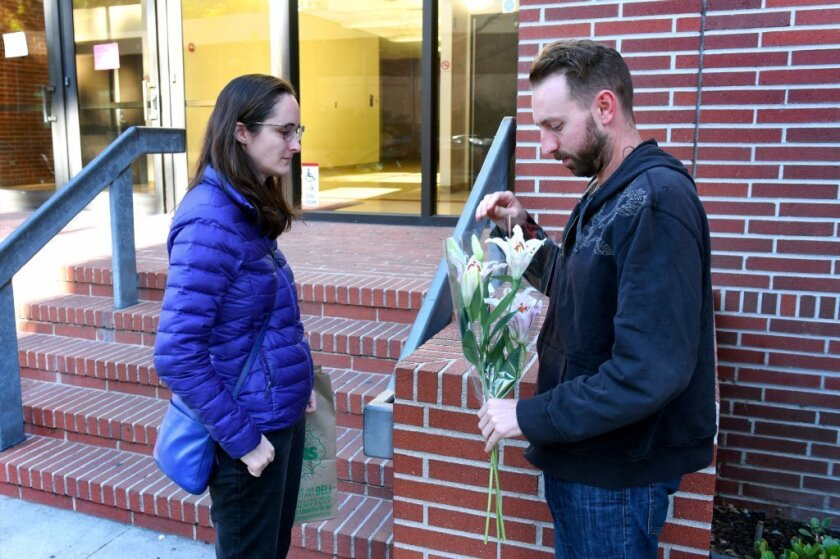 Dalton Combs, right, and Kate Swift-Spong bring flowers to the office of USC professor Bosco Tjan, who was stabbed to death Friday. A graduate student has been arrested in the slaying, according to the L.A. Police Department. Combs was Tjan's former student.
