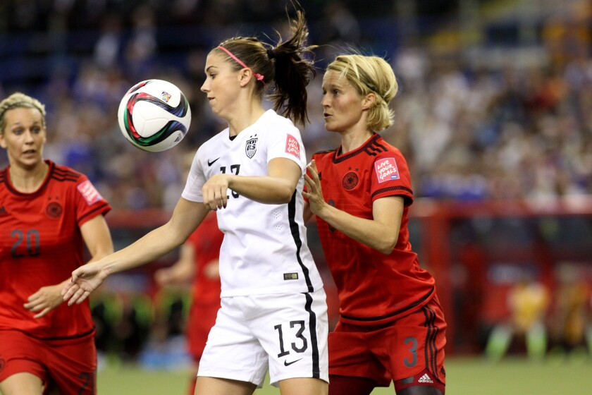 U.S. forward Alex Morgan gets control of the ball in front of German defender Saskia Bartusiak during the first half of a semifinal match at the Women's World Cup.