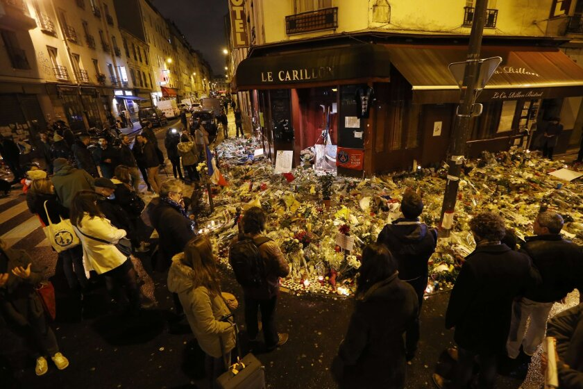 People gather at a makeshift memorial to the victims of the deadly attacks in Paris on Nov. 20. French President Francois Hollande plans to visit Washington asking for U.S. help, increasing the pressure on Obama to do more.