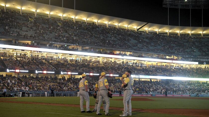 Several San Diego Padres players gather in the infield during a blackout in the 12th inning of a baseball game against the Los Angeles Dodgers,