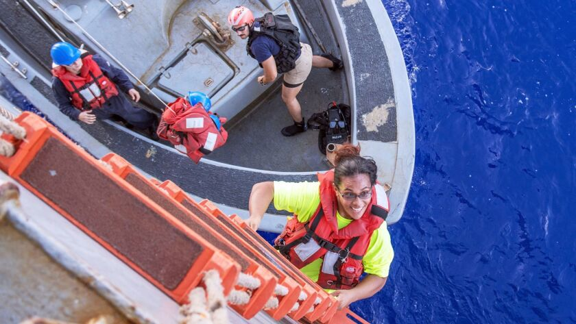 Tasha Fuiava climbs a ladder to board the Navy amphibious docking sup Ashland after being found at sea.