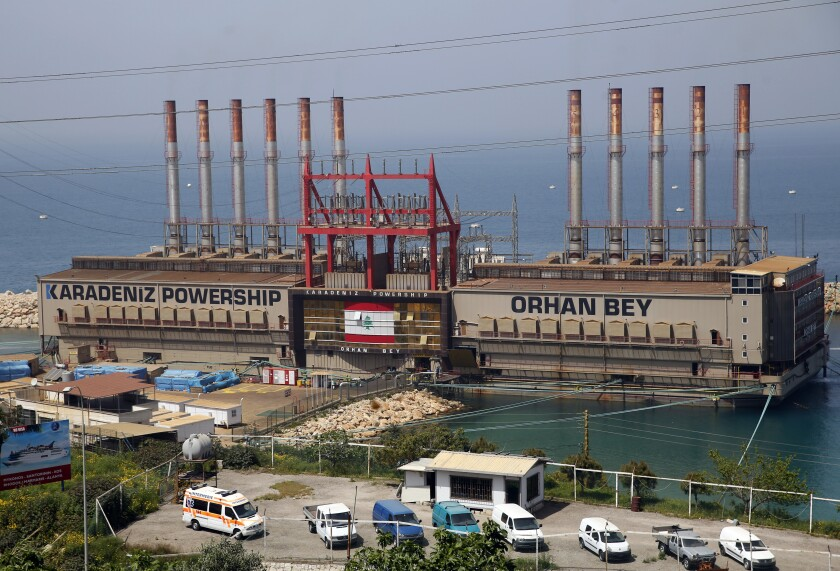 File - In this April 8, 2019, file photo, the Turkish floating power station Karadeniz Powership Orhan Bey, which generates electricity to help ease the strain on the country's woefully under-maintained power sector, is docked near the Jiyeh power plant, south of Beirut, Lebanon. The company Karpowership that operates the facility said Friday it has shut down it has suspended its operations, a move expected to increase outages in the crisis-hit Mediterranean country. (AP Photo/Hussein Malla, File)