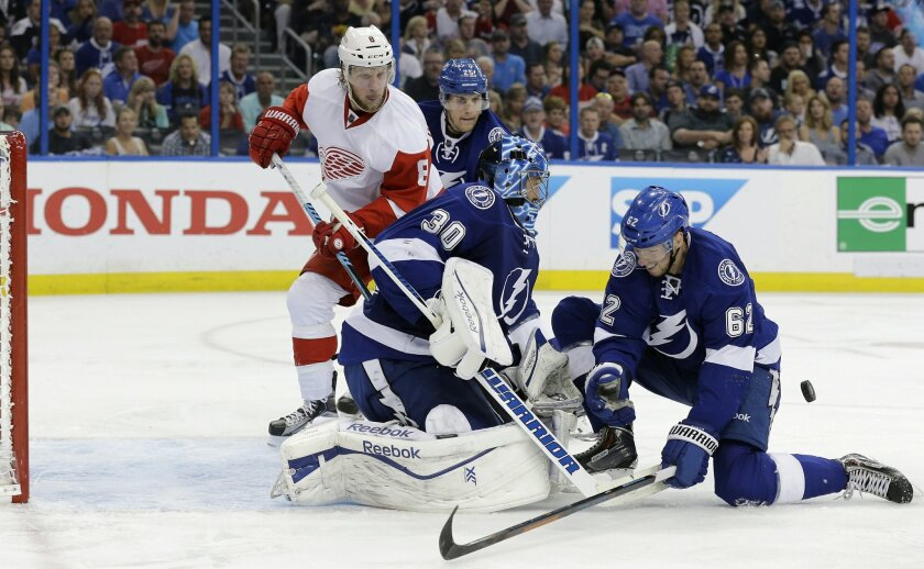 Tampa Bay Lightning goalie Ben Bishop (30) and defenseman Andrej Sustr (62), of the Czech Republic, stop shot by Detroit Red Wings left wing Justin Abdelkader (8) during the third period of Game 7 of a first-round NHL Stanley Cup hockey playoff series Wednesday, April 29, 2015, in Tampa, Fla. The L