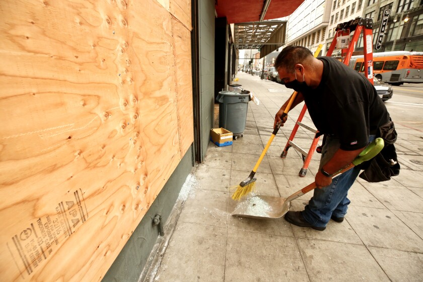 Juan Rodriguez boards up a store on Broadway in downtown L.A. on Tuesday morning after demonstrators vandalized windows.