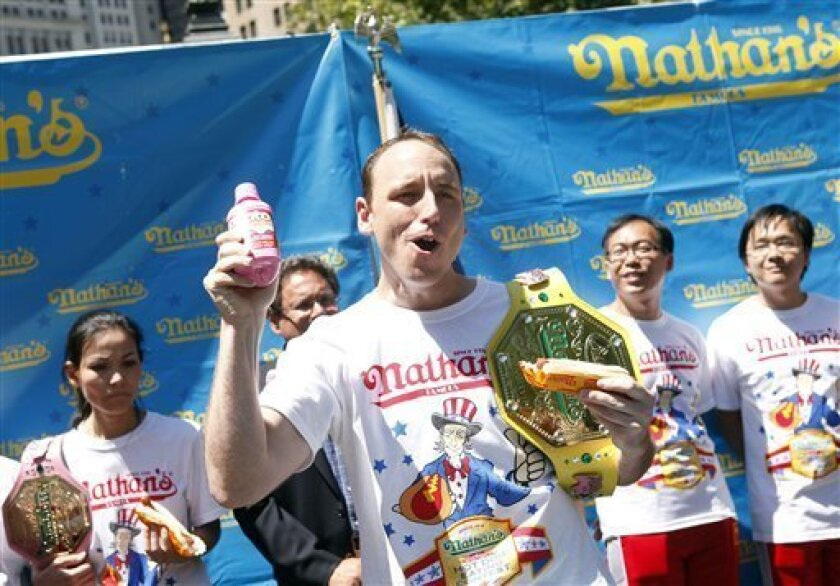 In this photo taken by AP Images for Pepto-Bismol, Joey Chestnut, favorite to win Nathan's Famous Fourth of July International Hot Dog Eating Contest, sponsored by Pepto-Bismol, reacts after his official weigh-in during a ceremony at City Hall Park, Friday, July 1, 2011 in New York. (Jason DeCrow/AP Images for Pepto-Bismol)