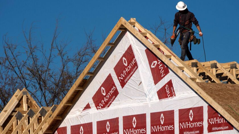 This file photo shows a construction worker installing a rooftop on to a new home being built in Fairfax, Va.