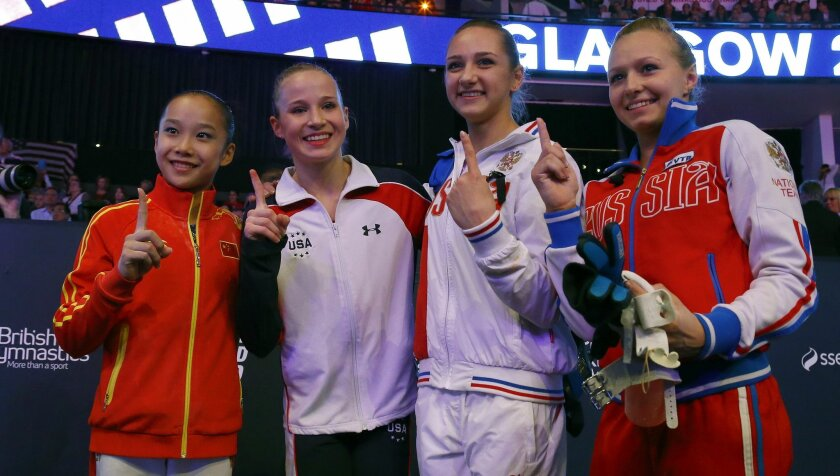 Four gold medal winners China's Fan Yilin, from left, Madison Kocian of the U.S., Russia's Viktoriia Komova and Russia's Daria Spiridonova pose after their uneven bars exercise at the women's apparatus final competition at the World Artistic Gymnastics championships at the SSE Hydro Arena in Glasgo