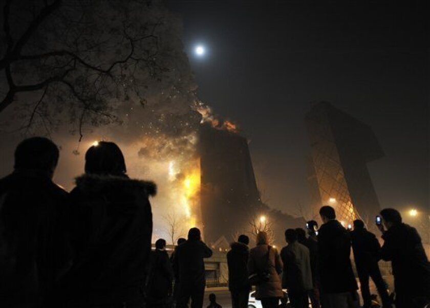 People gather to watch as unfinished Beijing hotel catches fire amid a holiday fireworks bonanza in Beijing, China, Monday, Feb. 9, 2009. The Mandarin Oriental hotel caught fire sometime before 9:00 p.m. (1300 GMT) on Monday night as the skies of the Chinese capital were filled with fireworks celebrating the lantern festival. The hotel, due to open this year, lies just north of Chinese Central Television's striking new headquarters building, also nearing the end of construction. (AP Photo/Andy Wong)