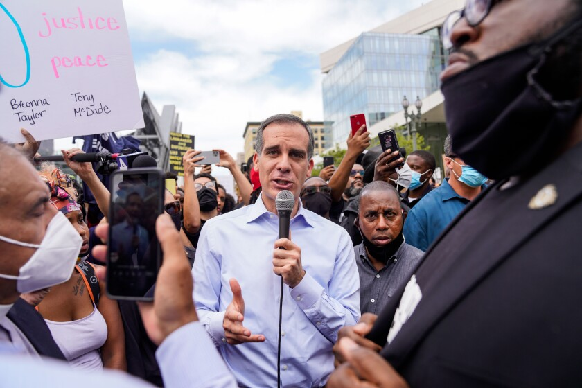 Mayor Eric Garcetti uses a microphone to speak to protesters outside Los Angeles City Hall