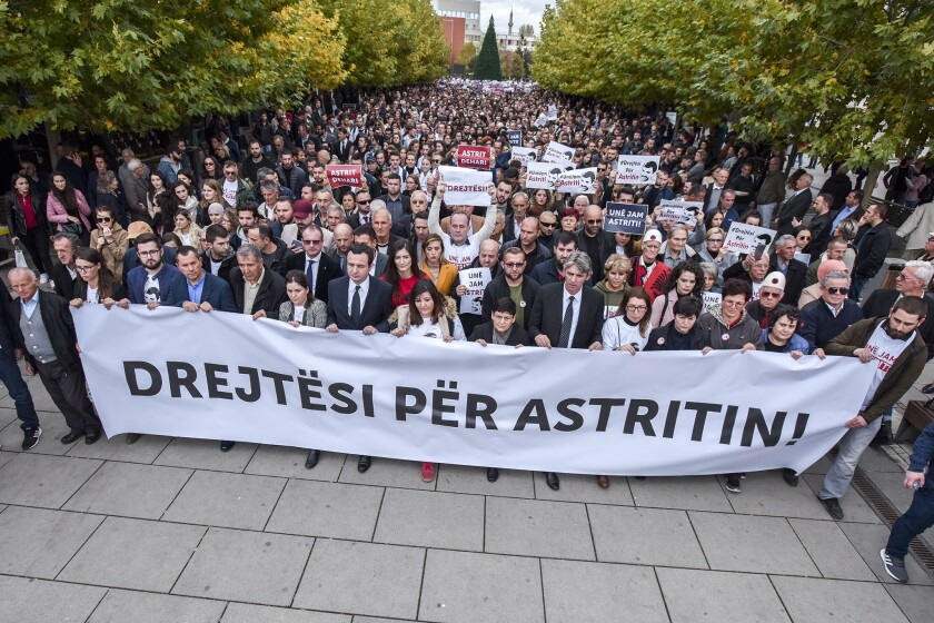 In this handout photo provided by the Vetvendosje Party, people hold up a sign reading 'Justice for Astrit' as they attend a rally in Pristina, Tuesday, Nov. 5, 2019. Hundreds of opposition supporters have gathered in the Kosovo capital demanding for justice for an activist who died in custody three years ago. The left-wing Self-Determination Movement, or Vetevendosje, held a peaceful protest in Pristina on Tuesday for Astrit Dehari, 26, who died in November 2016. (Vetvendosje Party via AP)