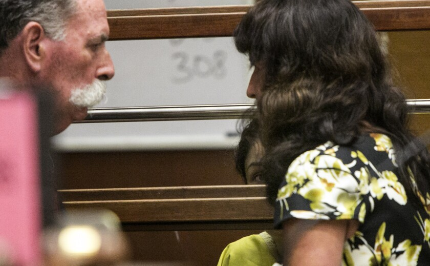 With her back to the court, Leyla Ors consults with her German interpreter during her arraignment.