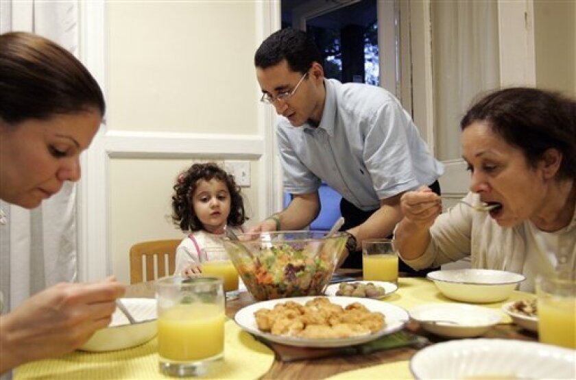 This Aug. 30, 2009 photo shows Saif Alnasseri, center, his daughter Sarah Alnasseri, 3, wife Zeinab Alrubaye, left, and mother Layla Alshawi, right, gather together to break their fast during Ramadan at their Plainfield, N.J. home. This is the first Ramadan the family will celebrate in the United S