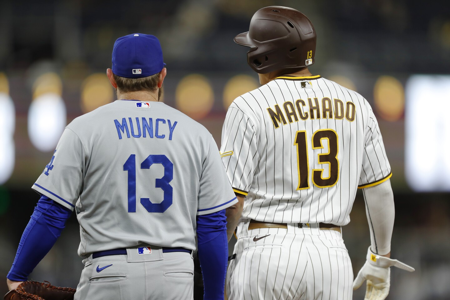 Los Angeles Dodgers' Max Muncy and San Diego Padres' Manny Machado stand at first base in the second inning.