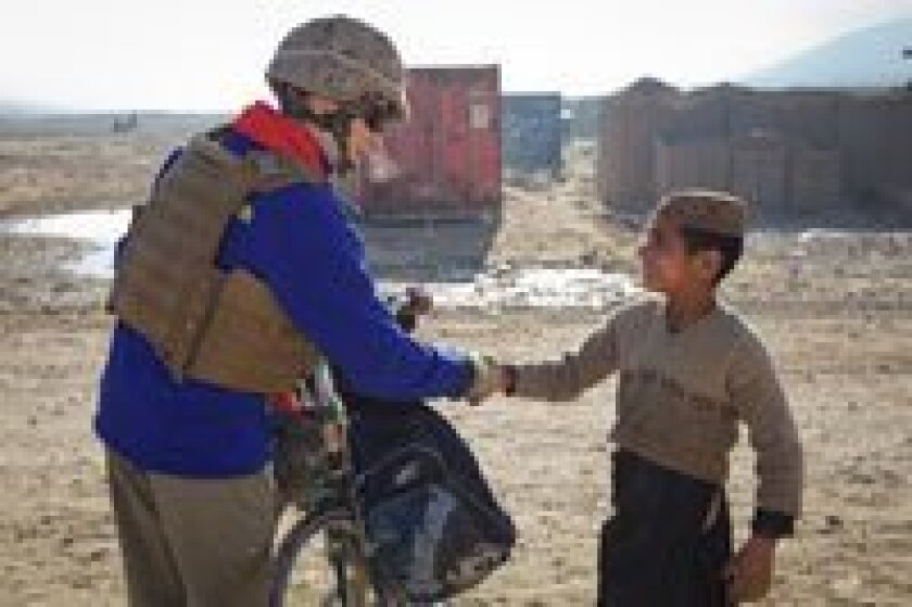 First Lady of the Marine Corps Bonnie Amos greets locals in Puzeh, Helmund Province, Afghanistan in December 2012.