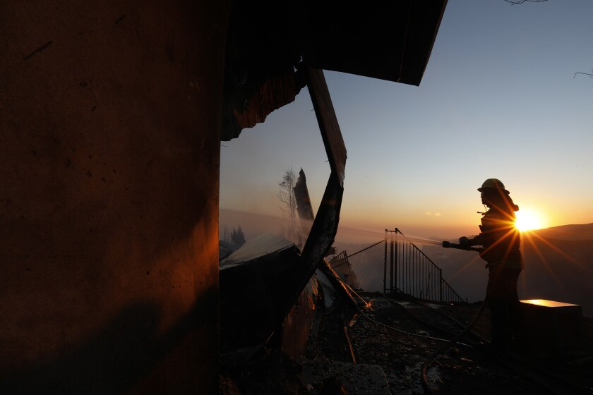 Firefighter Ken Williams puts out a hot spot on a fire-ravaged home along Linda Flora Drive in Bel-Air.