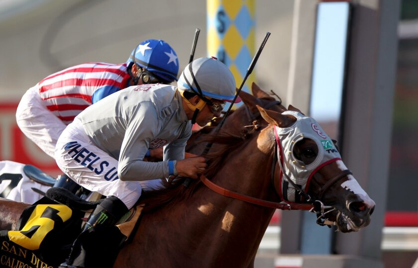 California Chrome, the 2014 Kentucky Derby and Preakness winner ridden by Victor Espinoza (6) edges Dortmund in the $200,000 San Diego Handicap on Saturday.