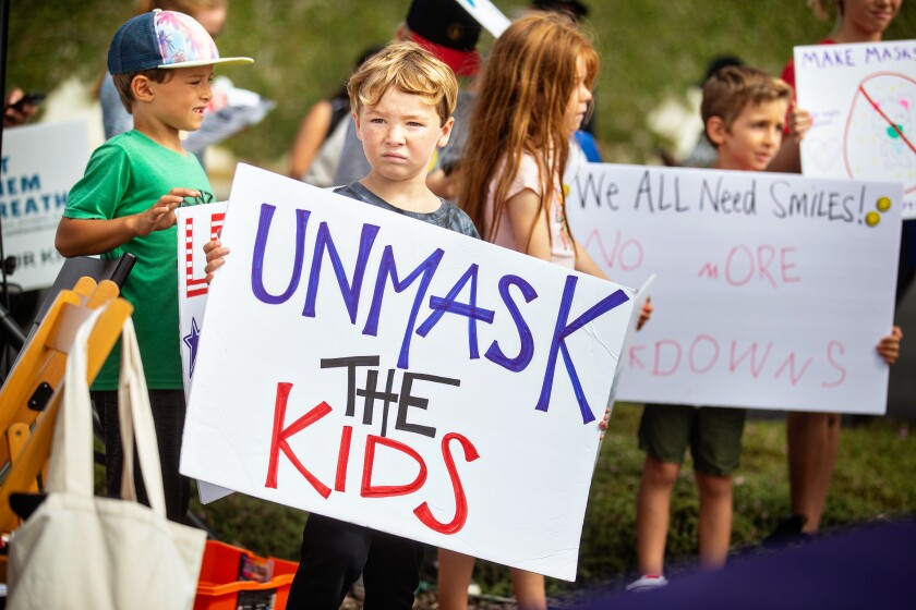 """A boy holds a sign that reads, """"Unmask the kids."""""""